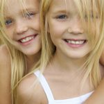 Portrait of cute girl embracing her twin sister and both looking at camera with a smile