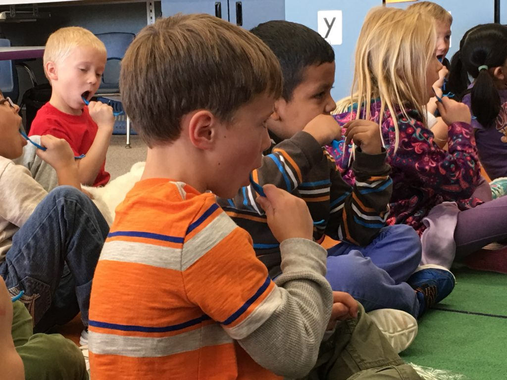 Kids flossing and brushing with Oh'Pal in the classroom