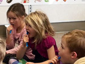5 year old boys and girls flossing in the classroom using Oh'Pal for a Cavity Free Future